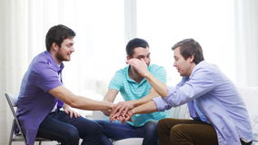 Smiling male friends with hands together at home stock footage