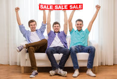 Smiling male friends holding sale sign Royalty Free Stock Photo