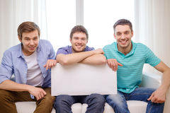 Smiling male friends holding white blank board Stock Photo