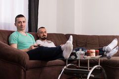 Smiling Male Friends Playing Video Games At Home Stock Images
