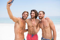 Smiling male friends taking selfie Stock Photos