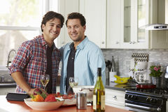 Smiling male gay couple preparing a meal look to camera Stock Photography