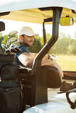 Smiling male golfer sitting in a golf cart Royalty Free Stock Photography