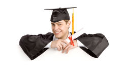 Smiling male graduate with diploma holding a sign. Smiling male student with diploma holding a sign at the white background Royalty Free Stock Images