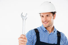 Smiling male handsome builder holding wrench. Smiling handsome builder holding wrench isolated on a white background Royalty Free Stock Photos