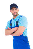 Smiling male handyman in coveralls standing arms crossed. Over white background Stock Photo