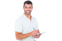 Smiling male handyman writing on clipboard. Portrait of smiling male handyman writing on clipboard over white background Stock Photos