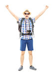 Smiling male hiker with raised hands gesturing happiness Royalty Free Stock Images