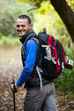 Smiling male hiker walking with hiking pole Royalty Free Stock Photos