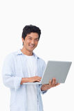 Smiling male with his laptop. Against a white background Royalty Free Stock Image
