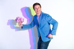 Smiling male holding beautiful nosegay. Portrait of beaming man with coloured shadow presenting attractive bouquet of flowers. Gift concept stock photo