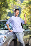 A smiling male holding a car key Royalty Free Stock Photo