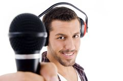 Smiling male holding microphone. On an isolated white background Royalty Free Stock Photos