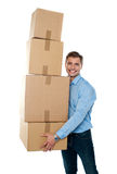 Smiling male holding stack of cartons Royalty Free Stock Photography