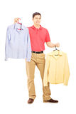 Smiling male holding two hangers with shirts. Full length portrait of a smiling male holding two hangers with shirts isolated on white background Royalty Free Stock Photo