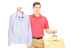 Smiling male holding two hangers with shirts. Isolated on white background Royalty Free Stock Images