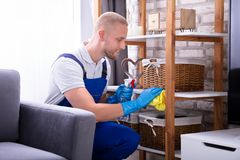 Male Janitor Wiping Wooden Shelf. Smiling Male Janitor In Uniform Wiping Wooden Shelf royalty free stock image
