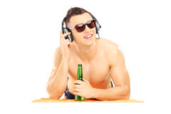 Smiling male lying on a beach towel listening music and drinking. Cold beer, isolated on white background Stock Image