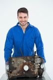 Smiling male machanic carrying old car engine Stock Photos