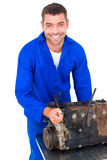 Smiling male machanic repairing car engine. Portrait of smiling male machanic repairing car engine on white background Stock Images