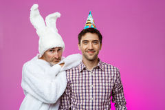 Smiling male and man in rabbit costume at birthday party over purple background. Royalty Free Stock Photo