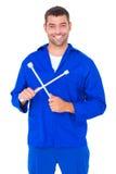 Smiling male mechanic holding lug wrench. Portrait of smiling male mechanic holding lug wrench on white background Stock Images