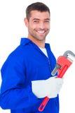 Smiling male mechanic holding monkey wrench. Portrait of smiling male mechanic holding monkey wrench on white background Royalty Free Stock Photo