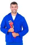 Smiling male mechanic holding monkey wrench. Portrait of smiling male mechanic holding monkey wrench on white background Stock Photos
