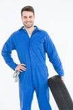 Smiling male mechanic holding tire Royalty Free Stock Images