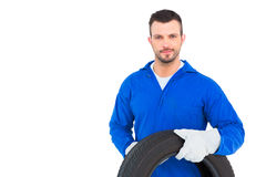 Smiling male mechanic holding tire Stock Images