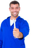 Smiling male mechanic showing spanner Royalty Free Stock Image