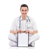 Smiling male medicine student holding a clipboard. Young male doctor showing a clipboard sitting on a floor with legs crossed and looking at camera. Full length Royalty Free Stock Photos