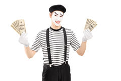 Smiling male mime artist holding US dollars and looking at camer Stock Photo