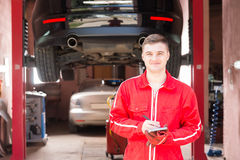 Smiling male motor mechanic standing making notes in front of a. Black sedan elevated on a hoist in a bay in a garage or workshop Royalty Free Stock Photo