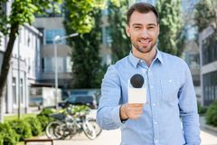 Free Smiling Male News Reporter Taking Interview With Microphone Stock Photography - 118803472