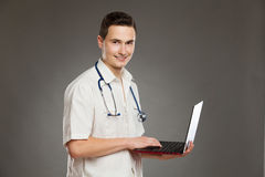 Smiling male nurse posing with laptop Stock Photo