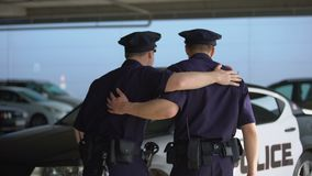 Smiling male officers giving high five and walking to police car, shift start stock footage