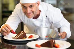 Smiling male pastry chef decorating dessert in kitchen Royalty Free Stock Photography