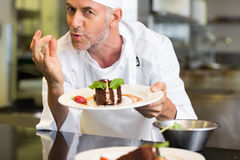 Smiling male pastry chef with dessert in kitchen Stock Images