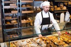 Smiling male pastry maker demonstrating croissant stock images