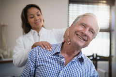 Smiling male patient receiving neck massage from female therapist. At hospital ward stock photos