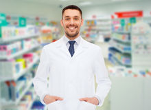 Smiling male pharmacist in white coat at drugstore. Medicine, pharmacy, people, health care and pharmacology concept - smiling male pharmacist in white coat over Royalty Free Stock Image