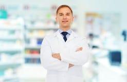 Smiling male pharmacist in white coat at drugstore Stock Images