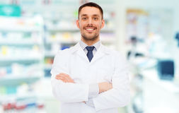 Smiling male pharmacist in white coat at drugstore. Medicine, pharmacy, people, health care and pharmacology concept - smiling male pharmacist in white coat over stock images