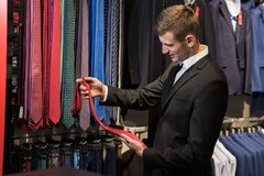 Man is picking up tie for suit in men`s shop. Smiling male is picking up tie for suit in men`s shop Royalty Free Stock Image