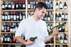 Smiling male professional wine expert holding wine bottles. In winery section in store Stock Photography