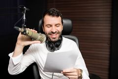 Smiling male radio host moderating. Male radio broadcaster talking on mic with a paper in hand Royalty Free Stock Image