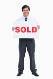 Smiling male real estate agent with sold sign. Against a white background Royalty Free Stock Images