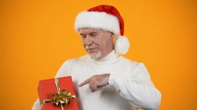 Smiling male retiree in santa claus hat pointing finger at red giftbox, discount. Stock footage stock video