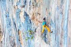 Smiling male Rock Climber descending on Rope with Okey hand sign. Smiling male Rock Climber hanging on Rope at vertical unusual shape and colour natural rocky Stock Photography